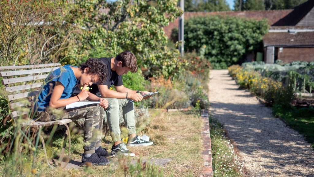 Students studying on a bench in the vegetable garden at Brockwood Park School