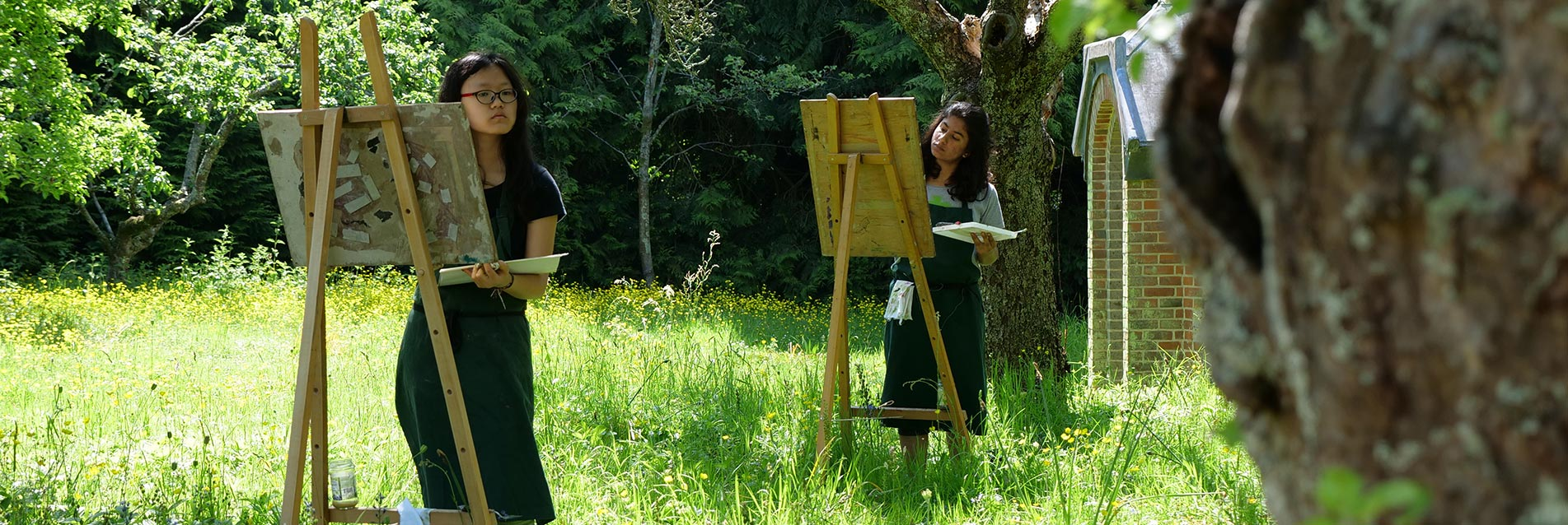 Two Brockwood Park School students painting outdoors