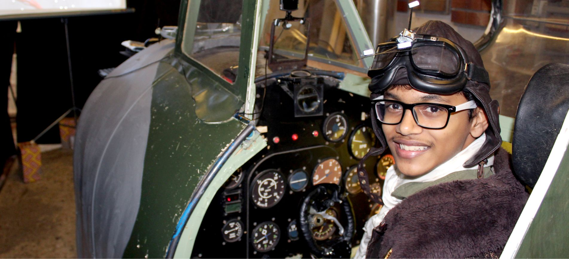 A young student at Brockwood Park School inside a mockup airplane