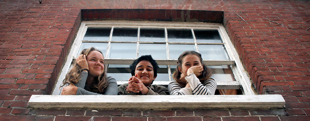 Three Brockwood Park School students looking from a window smiling