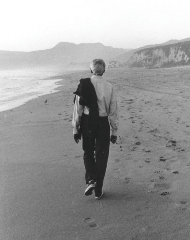 Krishnamurti seen from behind walking on a beach